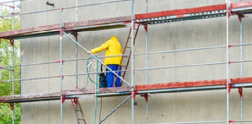 Men cleaning wall. Scaffolding, construction site in progress. Building renovation. Cleaning dirtiness.